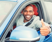 Man driver happy showing thumbs up coming out of car